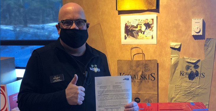 grocery worker giving thumbs up with union contract