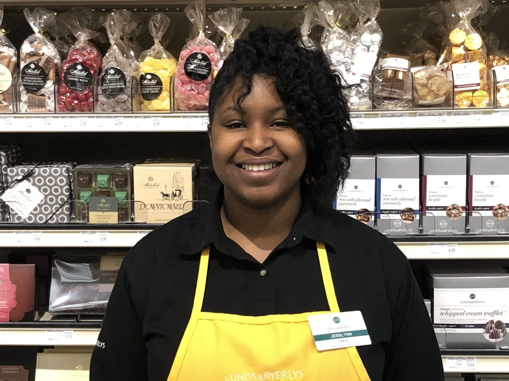 grocery worker standing in front of chocolate shelf